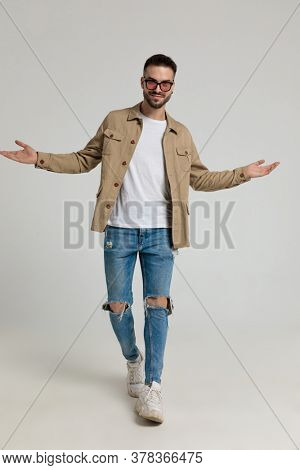young casual unshaved man in jacket wearing sunglasses, opening arms and welcoming, walking and posing on grey background