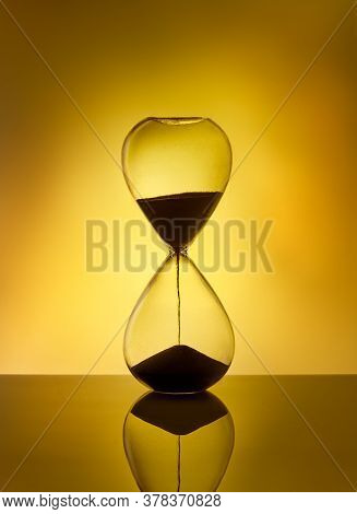Hourglass As Time Passing Concept For Deadline, Running Out Of Time. Sandglass On Yellow Background.
