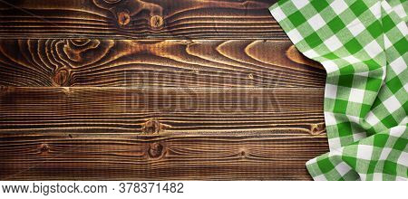 checked cloth napkin at old wooden plank board table background, top view
