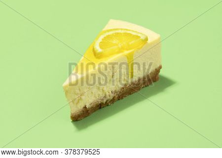 Cheesecake Slice With Lemon Sauce Dripping And Lemon Slice, Isolated On Green Background. Close-up O