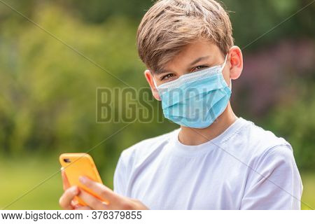 Boy teenager teen male child wearing a face mask outside during the Coronavirus COVID-19 virus pandemic while using his mobile cell phone for social media or text messaging