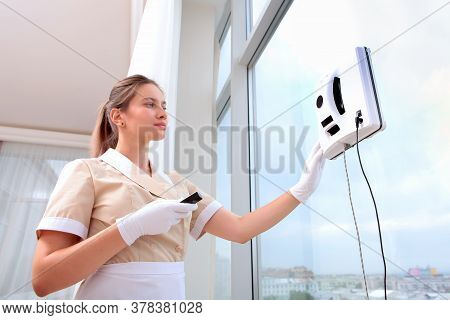 A Uniformed Maid Installs A Window Cleaner Robot On The Glass. Clear Window. Photos In The Interior.