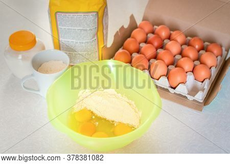 Flour With Eggs In Yellow Bowl On The Background Of Ingredients For Cooking A Cake Such A Sugar, Egg