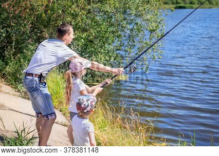 A Girl With Father And Brother Stand On The Shore Of The Lake With Rods And Catch Fish. Concept Of O
