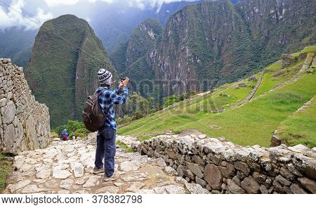 Traveler Taking Pictures Of The Ancient Agricultural Terraces Ruins In Machu Picchu Inca Citadel, Cu