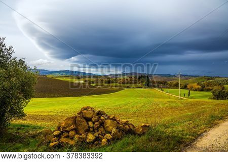 The thunderstorm begins. Flat rows of ploughed fields and meadows. Picturesque hills of the legendary Tuscany. Beautiful Italy. The concept of active, rural and photo tourism