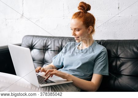 Portrait Of Smiling Redhead Young Woman Using Laptop At Home Sitting On Soft Sofa. Lady Is Working O