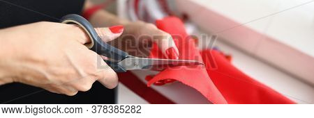 Close-up Of Qualified Female Dressmaker Cutting Red Cloth With Scissors. Working Moment In Fashion A