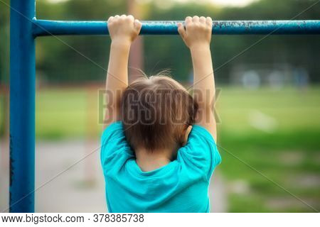 Toddler Boy Learning To Do Pull Ups: Preschooler Hanging On Worn-out Steel Bar At Sports Ground Outd