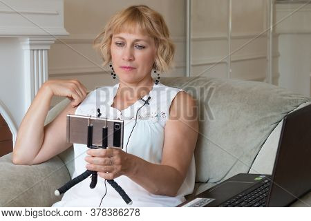A Beautiful Woman, A Fifty-year-old Blonde, Sits In A Chair And Holds A Smartphone In Her Hands