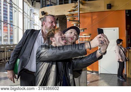 Kiev, Ukraine, 03.23.2020: Selfies Are Made By Two Men And A Girl. The Couple Sticks Out Their Tongu