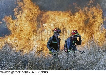 Two Firemen Wearing Their Uniforms In Front Of A Blaze