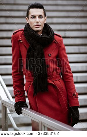 LGBTQ community lifestyle concept. Young homosexual man stands on a stairs. Handsome fashionable gay male model poses in cityscape outdoors. Wears red coat, gloves, and black scarf.