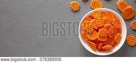 Overhead View, Fresh Raw Organic Carrot Chips In A White Bowl Over Gray Background. From Above, Over