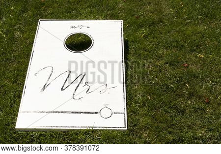 A White Cornhole Game On A Green Lawn With Mrs Written In Black As A Wedding Present.