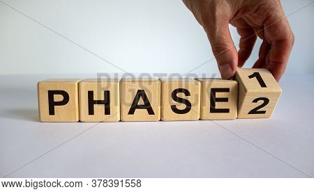 Time For Phase 2. Hand Is Turning A Cube And Changes The Word 'phase 1' To 'phase 2'. Beautiful Whit