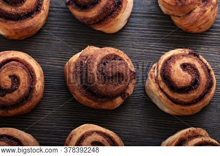 Freshly baked cinnamon rolls buns with spices on wood background. Christmas pastries. Close-up. Top view.