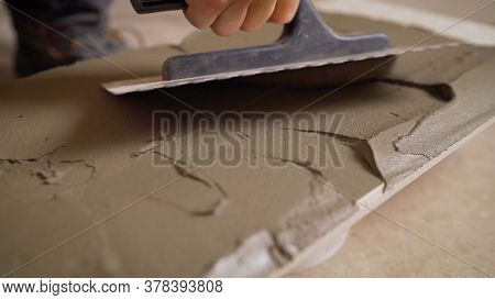 Master Applies The Adhesive For Ceramic Tiles. Laying Tiles In The Bathroom. A Worker Applies Adhesi