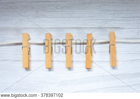 Light Brown Wooden Clothes Pegs Scattered On A Grey Table.