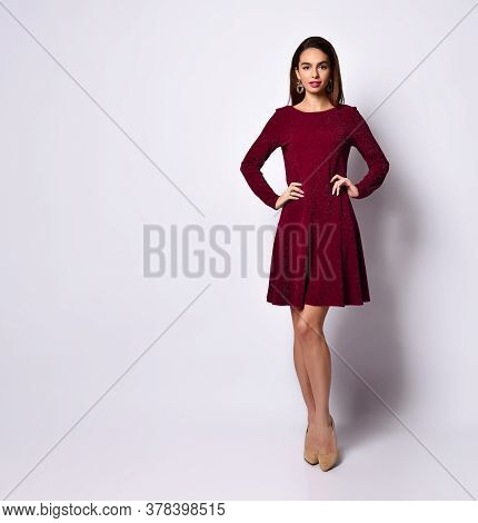 Gorgeous Dark-haired Young Woman Standing Hands On Hips In Elegant Dark-red Sequin Dress With Long S