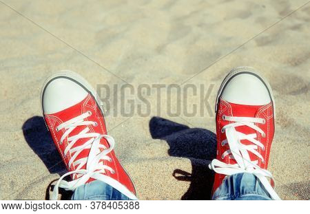 Two Legs In A Red Gym-shoes With White Laces, Against The Background Of Light Beach Sand On A Sunny