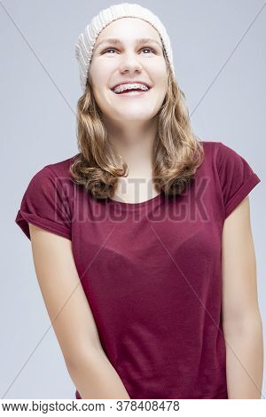 Teenage Ideas. Happy Laughing Caucasian Teenager Girl Wearing Teeth Brackets. Posing Against Gray.