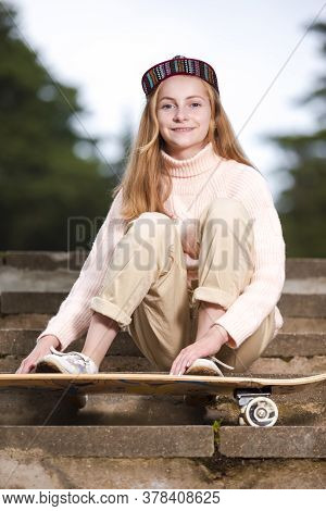 Teenager Lifestyle Concepts. Natural Portrait Of  Happy Caucasian Teenager Girl Posing With Longboar