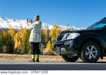 Hipster Woman In Hat Travel By Car On Autumn Road, Rent A Car In Vacations. Woman Photographing With