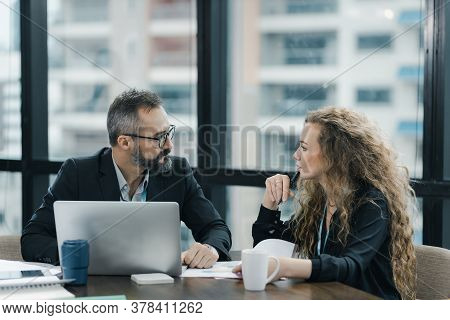 Young Manager Listening To His Colleague Explanations In Modern Co Working Office.