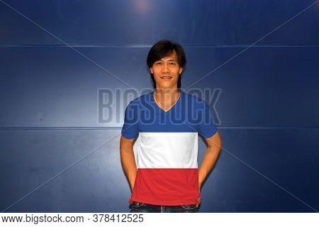 Man Wearing Yugoslavia (1918-1941) Flag On Shirt And Standing On The Blue Wall Background. Three Whi