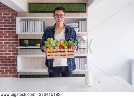 Young Man Is Holding A Basket Box Wooden With Colorful Vegetables And Fruits Organic To Prepare For