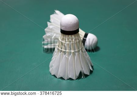 Used Shuttlecock Put Vertical And Out Focus Shuttlecock Put Horizontal On Green Floor Of Badminton C