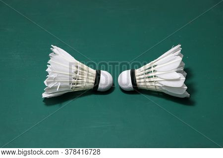 Two Used Shuttlecocks On Green Floor Of Badminton Court With Both Head Each Other, Concept Of Badmin