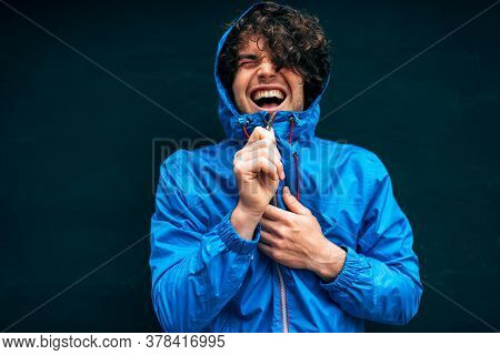 Happy Young Man Smiling Broadly, Wearing Blue Raincoat During Rain Outside. Cheerful Male In Blue Ra