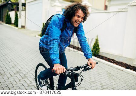 Image Of Handsome Cyclist Man Cycling On His Bike Down The Street Next To The House. Caucasian Male