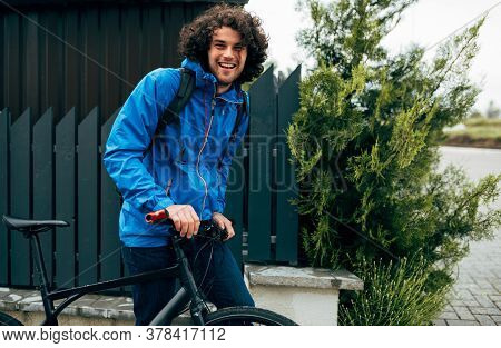 Young Man Walking With His Bike After Bicycling Down The Street On A Rainy Day Next To The Fence's H