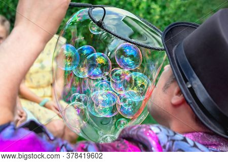 Man Artist And Magician In Black Hat Shows A Performance With The Inflation Of Soap Bubbles. Close-u