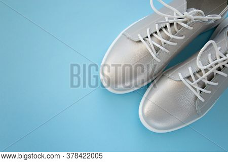 Pair Of New Metallic Silver Shoes With White Shoelaces Isolated On Blue Background, Top View. Copy S