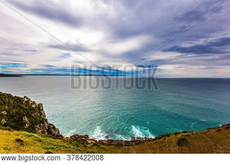 The picturesque coast of the Pacific Ocean. Sunset sky portends a storm. Nugget Point Lighthouse on the Cape Nugget. South Island, New Zealand. The concept of active, environmental and photo tourism