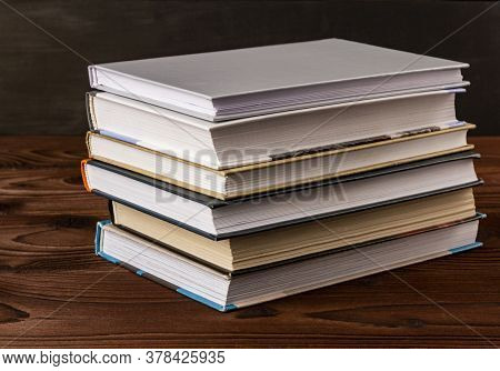 High Angle Close Up Of Stack Of Books On Wooden Table. Books In The Library On The Table. Literature
