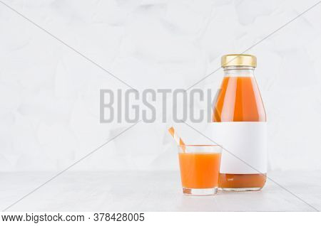 Vegetable Carrot Juice In Glass Bottle With Blank Label Mock Up With Glass, Straw On Wood Table In W