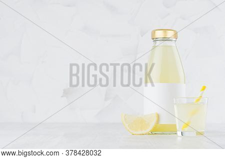 Yellow Lemon Juice In Glass Bottle Mock Up With Blank Label, Straw, Wine Glass, Fruit Slice On White
