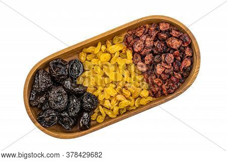Top View Of Various Kinds Of Dried Fruit In A Wooden Tray On White Background With Clipping Path.