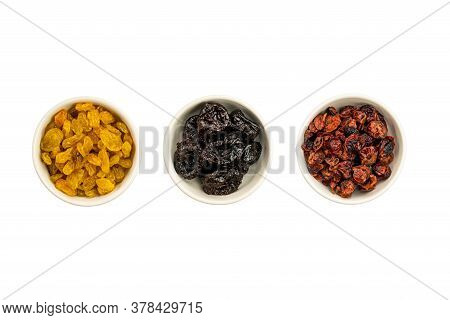 Top View Of Various Kinds Of Dried Fruit In White Ceramic Bowls On White Background With Clipping Pa