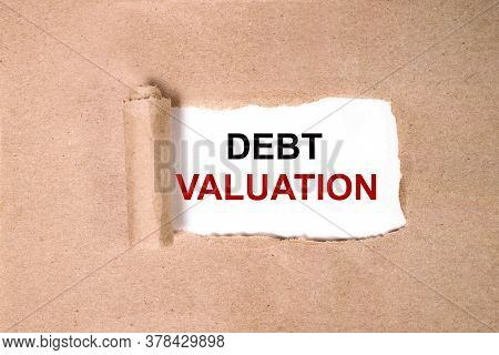 Debt Valuation. Inscription On A White Background On Torned Paper. Close-up