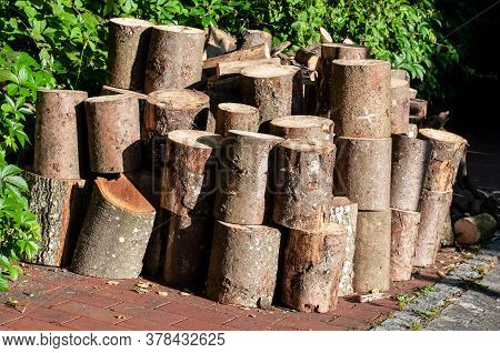 Close-up Of Fuel Wood Of Cut Tree Trunks Stacked Up In A Garden