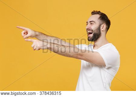 Side View Of Laughing Young Bearded Man Guy In White Casual T-shirt Posing Isolated On Yellow Backgr