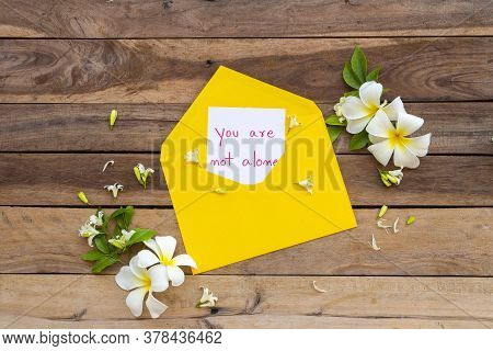 You Are Not Alone Message Card Handwriting In Yellow Envelope With Flowers Frangipani Arrangement Fl