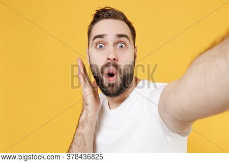 Close Up Of Shocked Young Bearded Man Guy In White Casual T-shirt Isolated On Yellow Wall Background