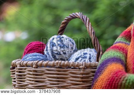 Red, Blue And White Woolen Balls In A Wicker Basket On A Multi-colored Knitted Blanket. Natural Back